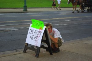A memphis zombie hides behind a therapy sign